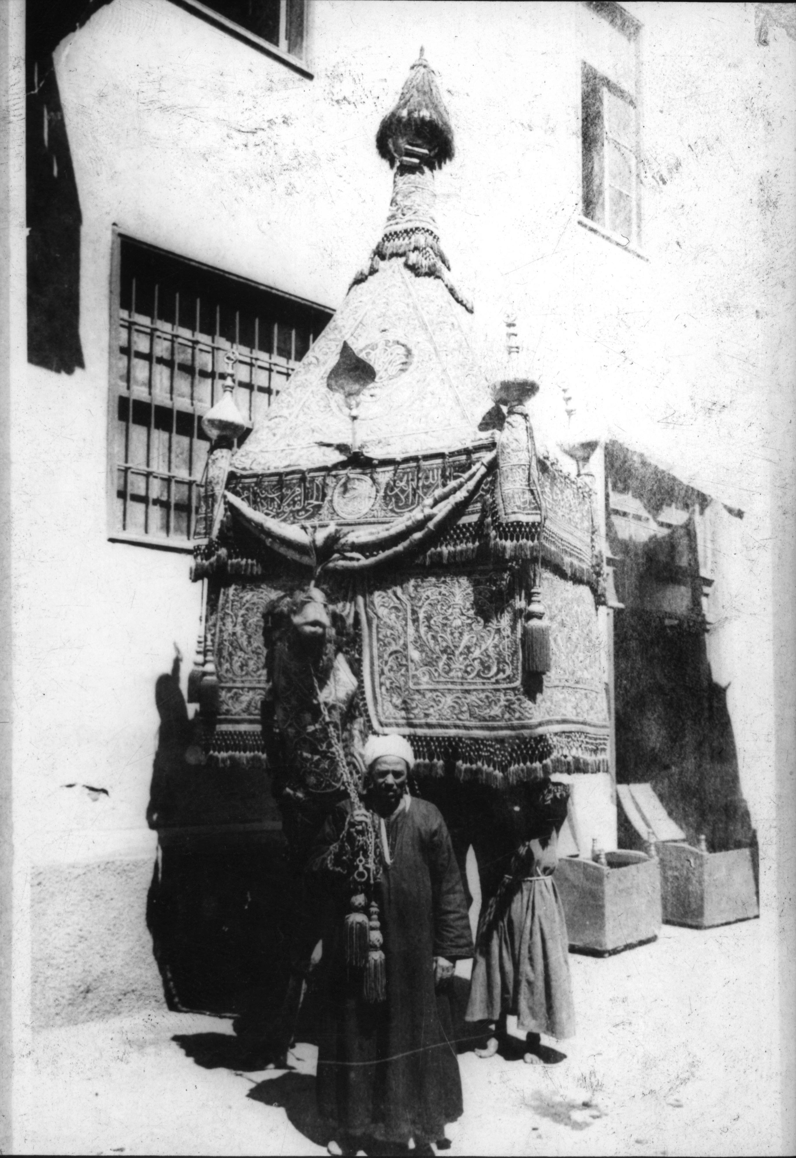 The mahmal on its camel with its caretaker in front of the Dar al-Kiswah