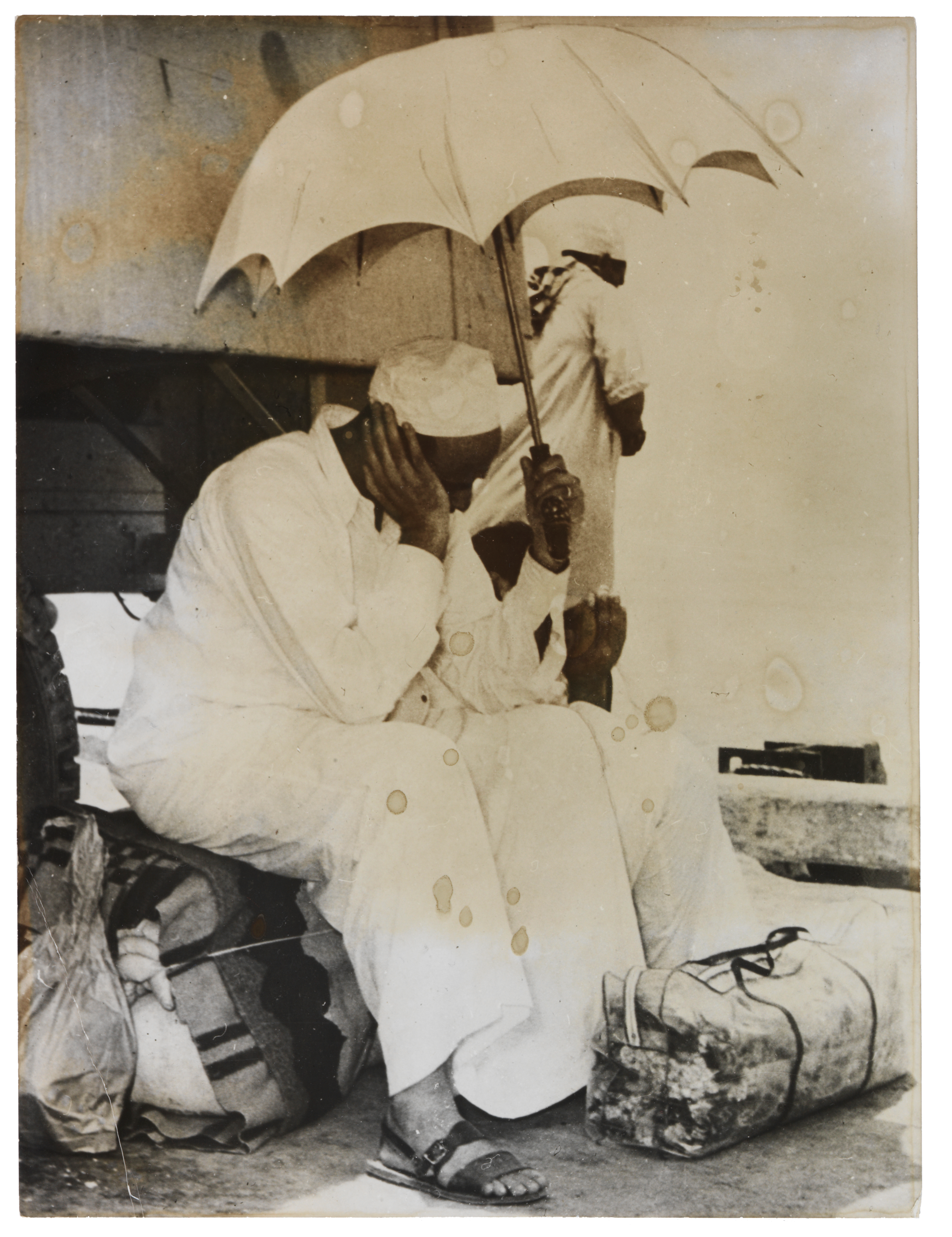 A pilgrim waiting with his luggage, possibly at Suez